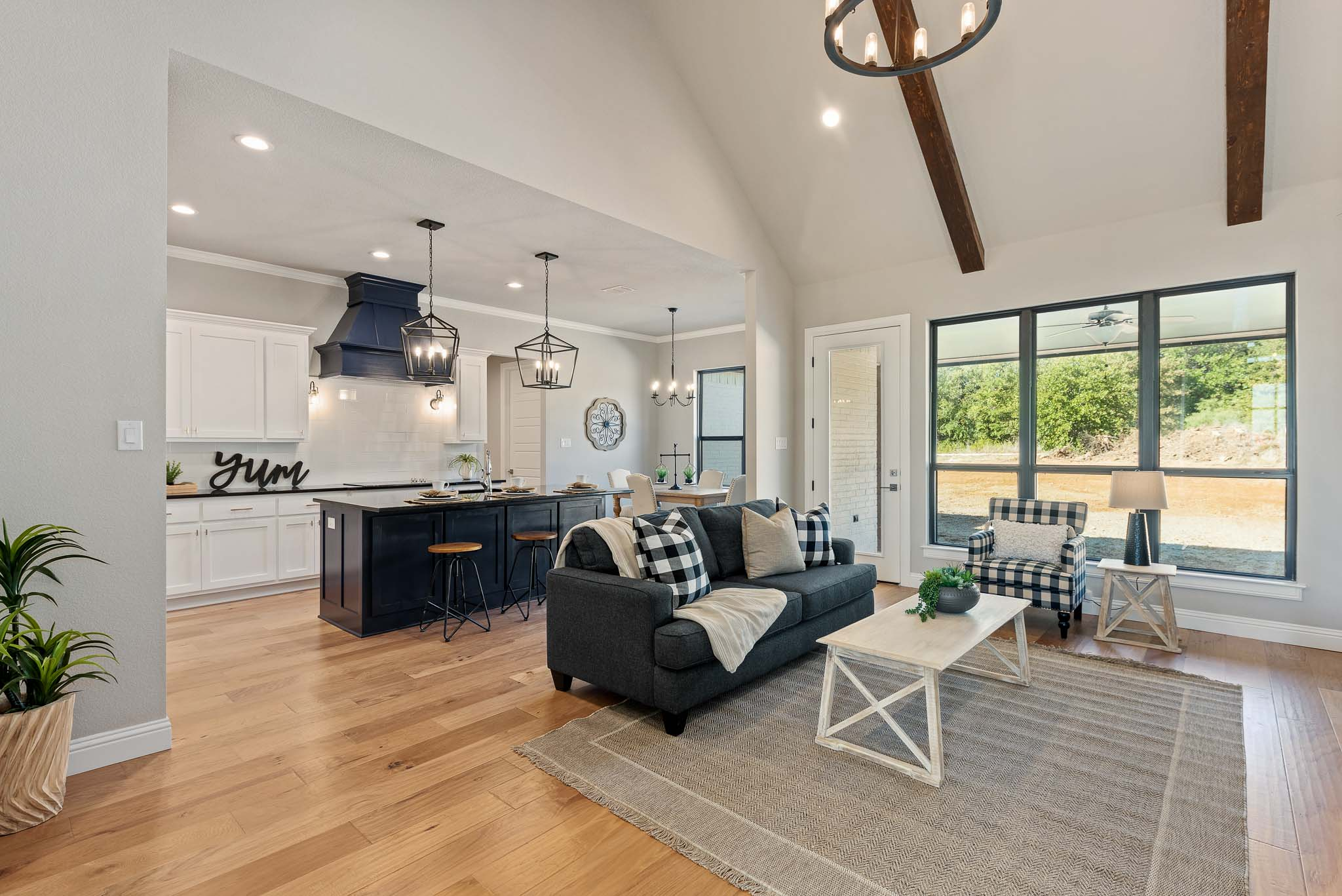 Farm style home living room with high ceiling and wood beams